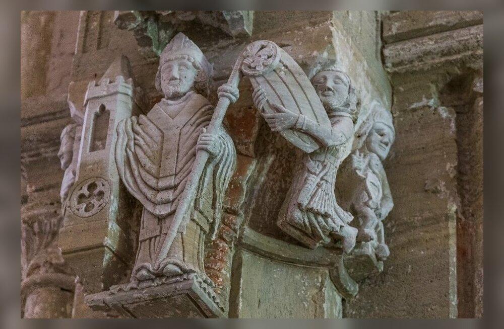 Püha Nikolause skulptuurgrupp Karja kirikus. Püha Nikolaus on kaupmeeste kaitsepühak. Kas põlvitav kaitsealune tema vasakul käel võiks olla soolakaupmees oma soolalaevaga, kes kurseeris taga Karja kirikut Soela väina läbival veeteel? Nuiamees seisab laeva
