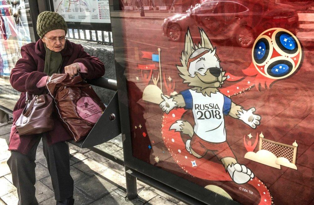 Pensionär Moskva bussipeatuses jalgpalli maailmameistrivõistluste maskotti Zabivakat kujutava reklaami kõrval. Linnades, kus MM-i mängud toimusid, protestida ei lubatud.