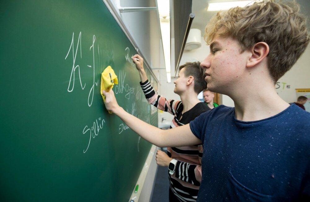 Kehra gümnaasiumi 9.a õpilased demonstreerisid tahvlil, kuidas allkirja anda. Taustal näitab ette õpetaja Reesi Kuslap, esiplaanil lihvib autogrammi Keijo-Johann.