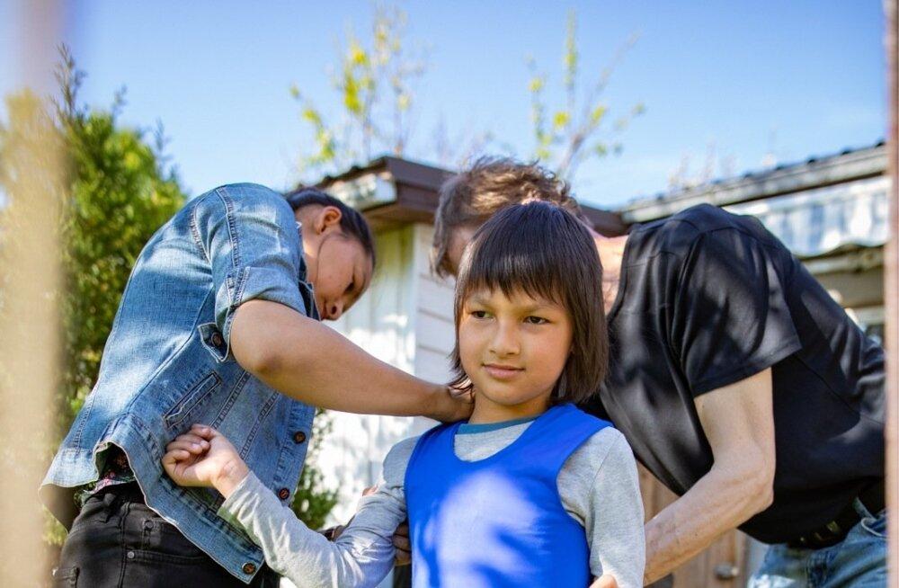 Vanemad üritavad pojale tugivesti selga panna, kuid see on talle väikseks jäänud. Arstide kinnitusel vajab laps tugivesti, kuid ametnike sõnul pole see talle vajalik.