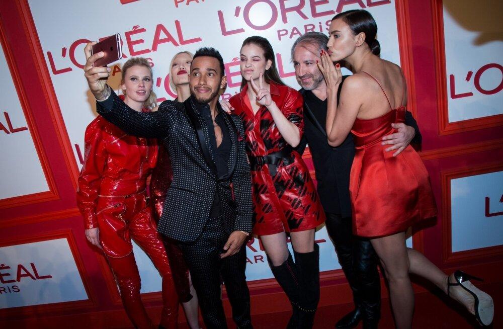 Lewis Hamilton (esiplaanil) poseerib koos modellidega. Seekord on ta näitsikutega pildile püütud Pariisis.