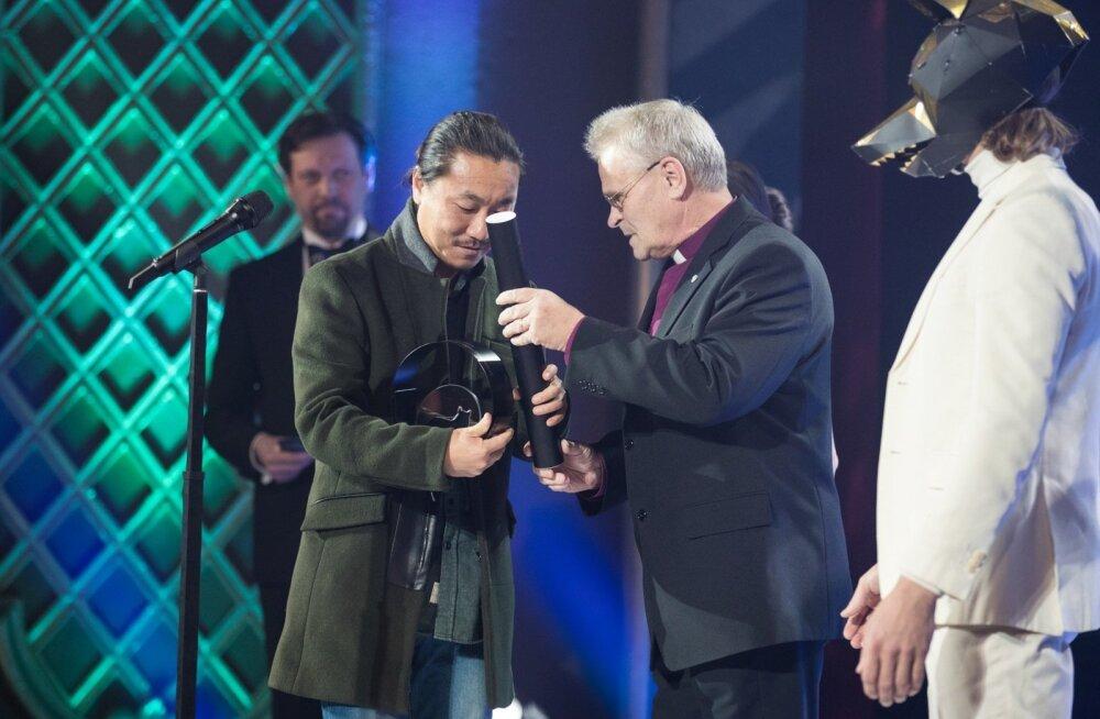 """Filmi """"Ekskavaator"""" režissöör Ju-hyoung võtab Andres Põdralt vastu vaimulike auhinna."""