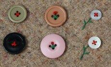 Esmalt kinnitage nööbid nii, et moodustuksid lillevars ja lehed. Õie tegemiseks on kasutatud suurt niidisõlme.
