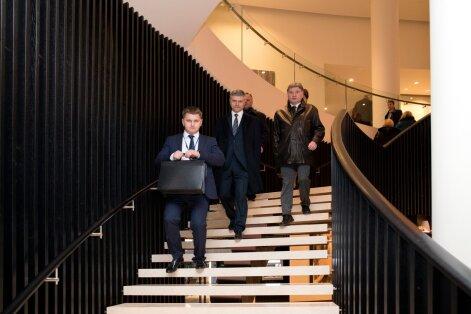 Oleg Belozerov (keskel) lahkus pärast istungit kaaskonnaga jooksujalu Hiltoni hotellist, et suunduda lennujaama.
