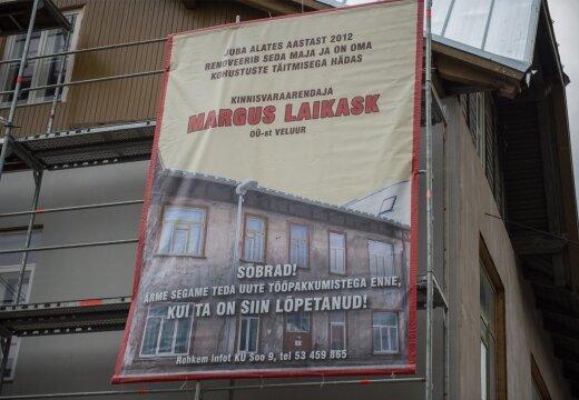 Korterihistu juhib avalikkuse thelepanu arendaja tegematajtmistele maja klge kinnitatud plakatiga